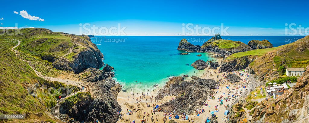 Cornwall crowds of tourists enjoying holiday sunshine Kynance Cove panorama stock photo