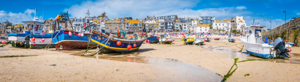 Cornwall St Ives fishing boats and tourists beach harbour panorama Fishing boats moored on the beach in St. Ives harbour, the picturesque seaside resort and fishing village in Cornwall, UK. sailing dinghy stock pictures, royalty-free photos & images