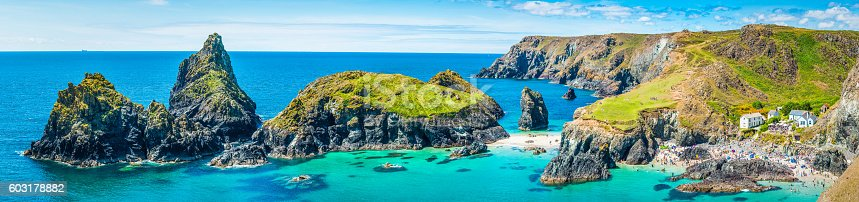 Crowds of tourists enjoying the summer sunshine amongst the dramatic sea stacks and rocky cliffs overlooking the turquoise ocean and idyllic sandy beaches of Kynance Cove, Cornwall, UK.