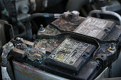 Damaged and coroded car battery danger