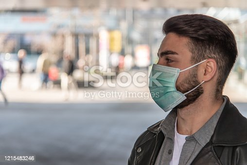 istock Corona - Covid-19 conceptual image of a man with a beard wearing a face mask - people in the background 1215483246