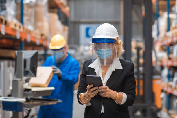 Corona practices for a female manager and male warehouse worker stock photo