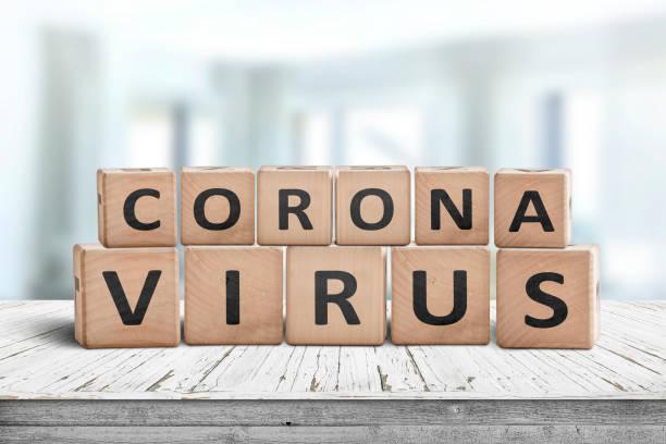 Corona virus alert message on a worn wooden desk stock photo
