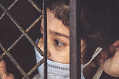 istock COVID-19 corona virus concept, little girl in medical mask looking through window at home. Sad kid during quarantine due to COVID. 1221847918