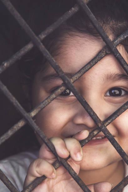 COVID-19 Corona-Virus-Konzept, kleines Mädchen in medizinischer Maske blick durch das Fenster zu Hause. lächelndes Kind während der Quarantäne aufgrund von COVID. – Foto