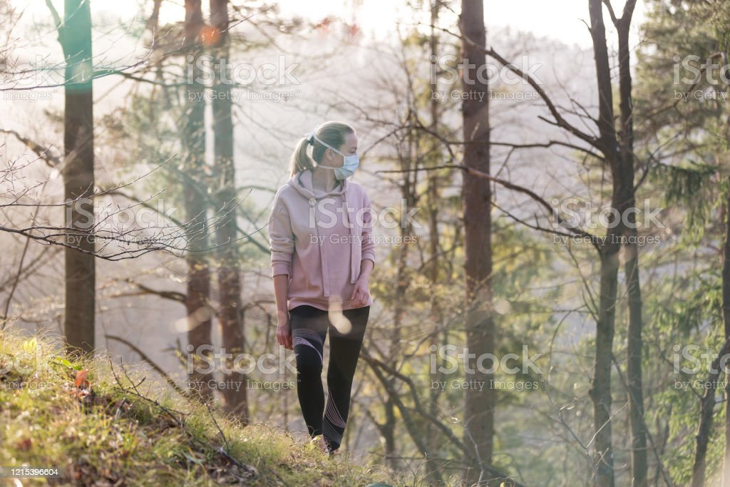 Corona-Virus, oder Covid-19, breitet sich auf der ganzen Welt aus. Porträt einer kaukasischen sportlichen Frau, die eine medizinische Schutzmaske trägt, während sie im Wald spazieren geht. Corona-Virus. - Lizenzfrei Allergie Stock-Foto