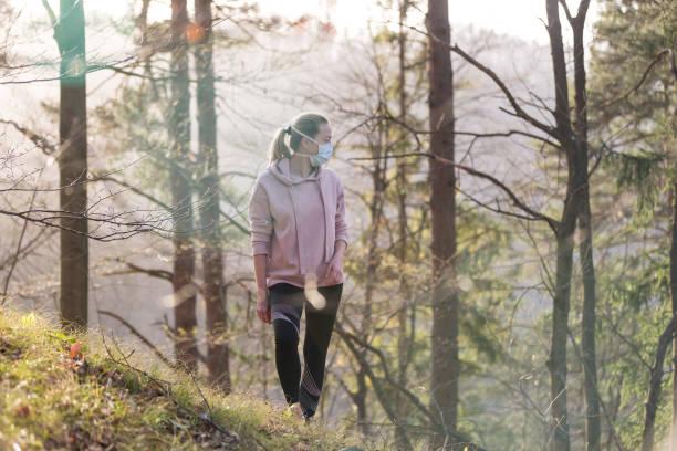 Corona-Virus, oder Covid-19, breitet sich auf der ganzen Welt aus. Porträt einer kaukasischen sportlichen Frau, die eine medizinische Schutzmaske trägt, während sie im Wald spazieren geht. Corona-Virus. – Foto
