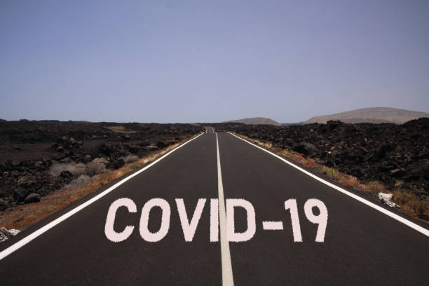 corona virus incerto perspectiva sombria conceito símbolo: estrada infinita através do deserto com palavra covid-19 - longo - fotografias e filmes do acervo