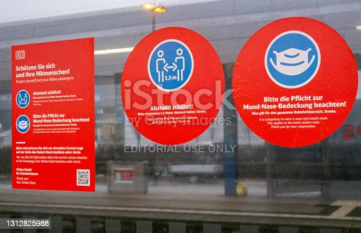 Bielefeld,Germany,02022021:Sticker of the Deutsche Bahn, with warnings about infection protection because of the corona pandemic on a pane of glass on the main train station in Bielefeld Germany.