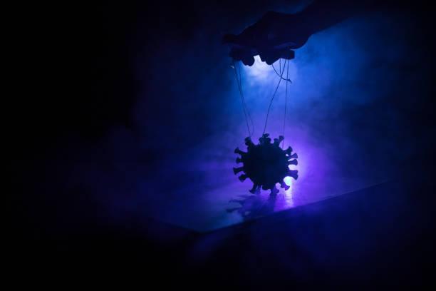 Coronavirus 2019-nCov novel coronavirus concept. Crowd looking on big Corona virus model at night with fog and backlight. Creative artwork decoration. Selective focus. – zdjęcie