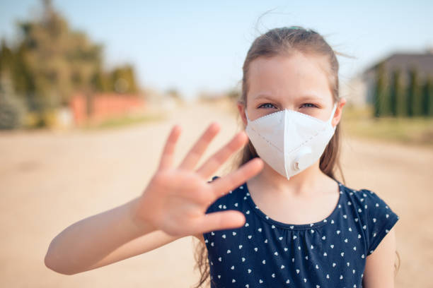 Coronavirus and air pollution concept. Little Caucasian girl wearing face mask for protection stock photo