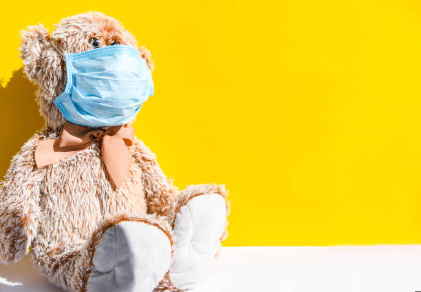 Coronavirus and Air pollution pm2.5 concept. Teddy bear in protection face mask isolated on yellow background with copy space stock photo