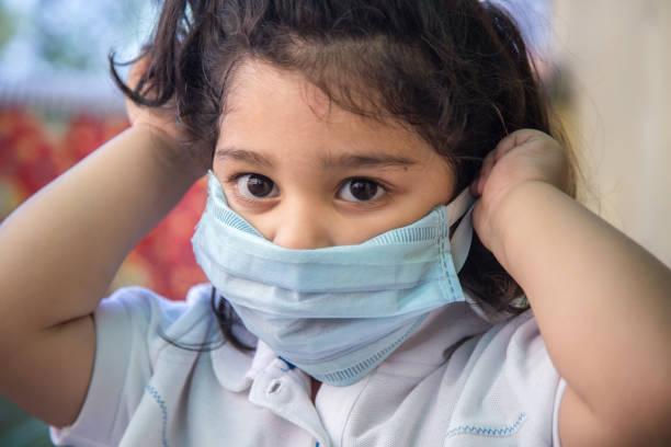 Coronavirus und Luftverschmutzung pm2.5 Konzept. Kleine indische Mädchen trägt Maske für Corona-Virus-Ausbruch zu stoppen. Wuhan Coronavirus und epidemische Virussymptome. – Foto