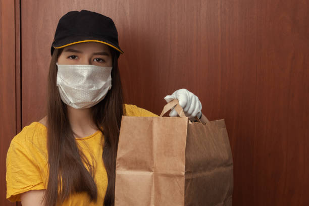 Coronavirus and quarantine. Safe Delivery of mail orders. Young woman courier in uniform in a medical antibacterial mask and gloves stands at the door with a package stock photo