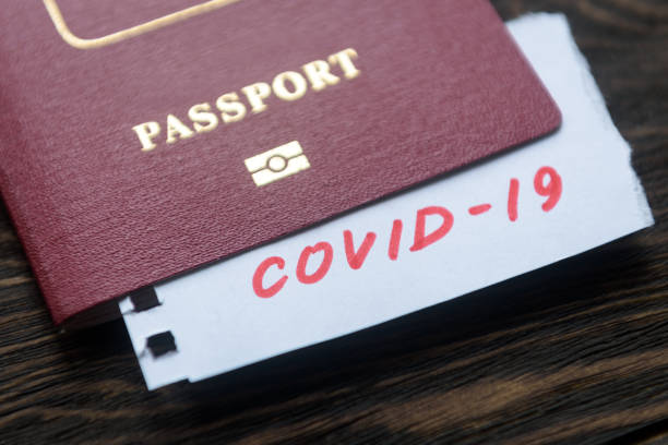 Coronavirus and travel concept. Note COVID-19 coronavirus and passport. Novel corona virus outbreak. Epidemic in Wuhan, China. stock photo