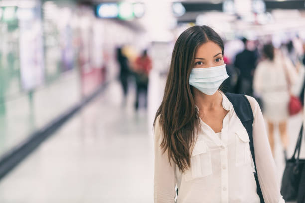 Coronavirus Asian woman walking with surgical mask face protection walking in crowds at airport train station work commute to hospital stock photo