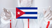 Healthcare personnel is holding Cuban Flag shaped surgical mask.