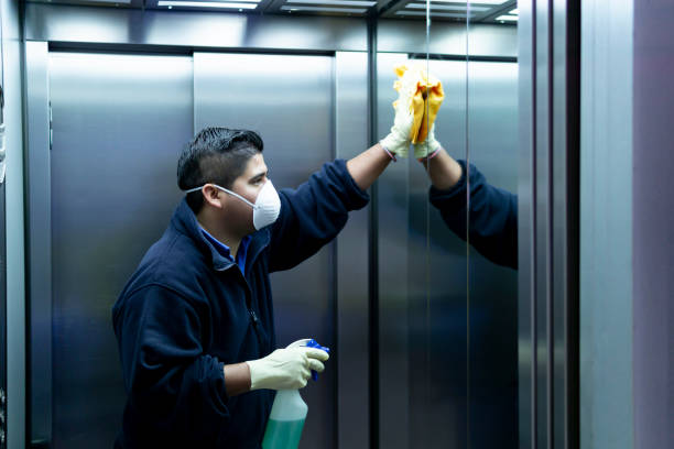 coronavirus. cleaning staff disinfecting elevator to avoid contagion coronavirus. cleaning staff disinfecting elevator to avoid contagion cleaner stock pictures, royalty-free photos & images