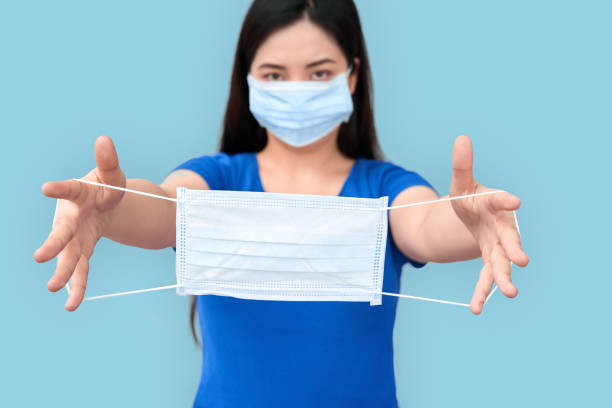 Coronavirus Concept. Chinese woman in medical mask standing isolated on grey givinganother mask to camera close-up stock photo