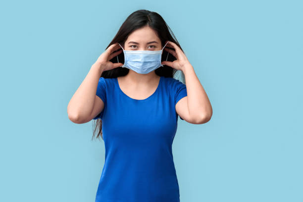 Coronavirus Concept. Chinese woman putting on medical mask standing isolated on grey smiling positive stock photo