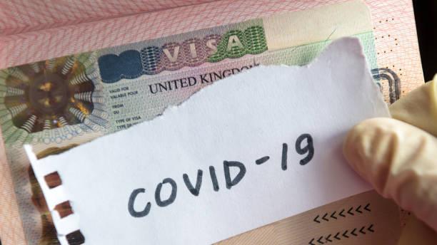 Coronavirus concept. Note COVID-19 coronavirus and UK visa in passport. Border control and quarantine of tourists infected with coronavirus. stock photo