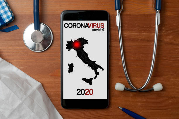 coronavirus concept: smartphone showing a map of italy with a red dot on the region where the spread of th infection start. stethoscope and a medical mask on a wooden table - lombardia foto e immagini stock