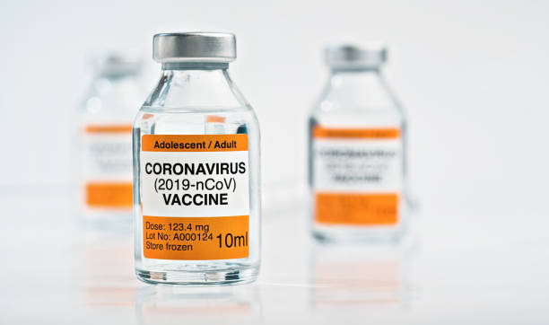 Coronavirus Covid 19 vaccine concept - small glass vials with silver caps on white table, closeup detail (own sticker design with dummy data - not real product) stock photo