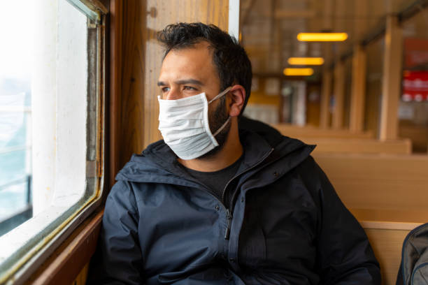 Coronavirus, covid 2019, young man with respiratory mask traveling in the public transport by ferry stock photo