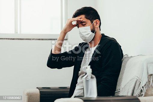 istock Coronavirus, covid-19 and quarantine concept. Sick man with headache symptom 1215583562