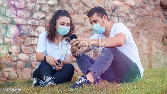 Coronavirus COVID-19 Beautiful Couple Wearing Medical Masks During Outbreak, - New normal lifestyle concept, social concept - Vivid filter