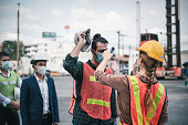 istock Coronavirus Covid-19 Disease Epidemic Crisis Situation, Construction Worker Having Fever Body Scan by Thermometer Scanning at Construction Site. Corona-Virus Covid19 Prevention of New Normal Concept 1226035043
