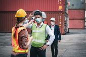 istock Coronavirus Covid-19 Disease Epidemic Crisis Situation, Container Shipping Worker Having Fever Body Scan by Thermometer Scanning at Ship Yard. Corona-Virus Covid19 Prevention of New Normal Concept 1226029245
