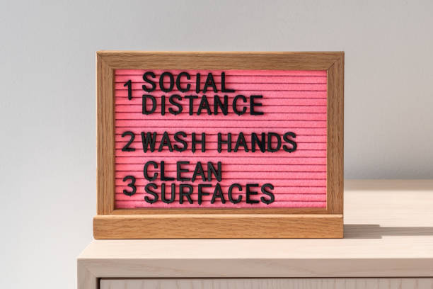 Coronavirus COVID-19 health safety guidelines. Text board in public space with rules, practice social distancing, wash hands often, clean surfaces, sanitizing surface, hand washing, stay home stock photo