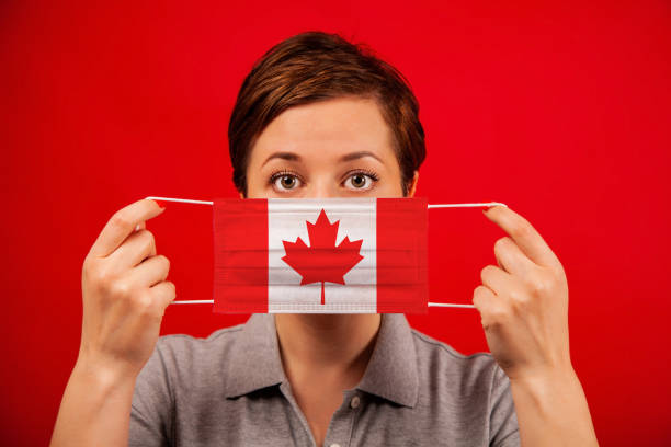 Coronavirus COVID-19 in Canada. Woman in medical protective mask with the image of the flag of Canada. stock photo