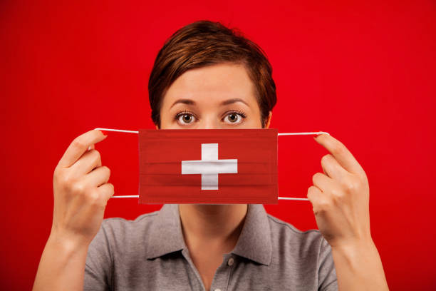 Coronavirus COVID-19 in Switzerland. Woman in medical protective mask with the image of the flag of Switzerland. stock photo