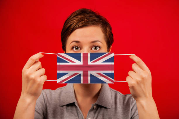 Coronavirus COVID-19 in the UK. Woman in medical protective mask with the image of the british flag. stock photo