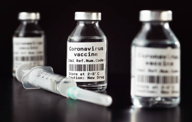 Coronavirus Covid-19 vaccine concept -  three glass vials on black table, hypodermic syringe needle near, closeup detail (label own design - dummy data and barcode, not real product) stock photo