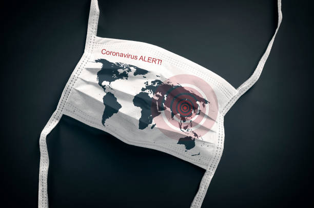 Coronavirus Covid-19 white face mask with a map of the world lying on a black background stock photo
