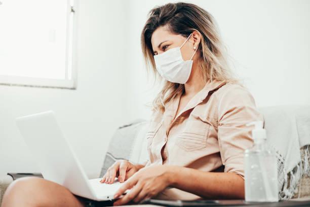Coronavirus. Covid-19. Frau in Quarantäne trägt Schutzmaske mit Laptop im Wohnzimmer. Flasche Alkoholgel im Vordergrund. – Foto