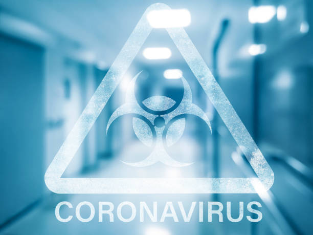 Coronavirus dangerous sign Coronovirus triangle biohazard warning sign on a blurred background of the hospital interior covid icon stock pictures, royalty-free photos & images
