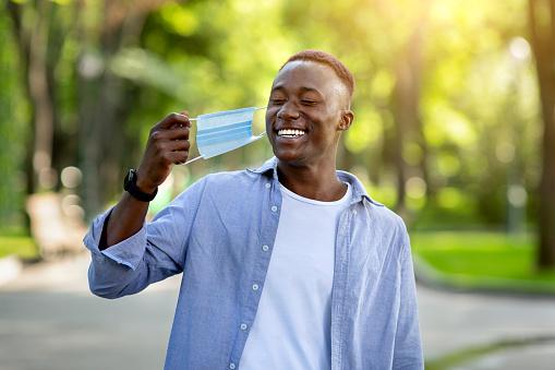 Coronavirus epidemic is over. Smiling black man removing his medical mask at city park