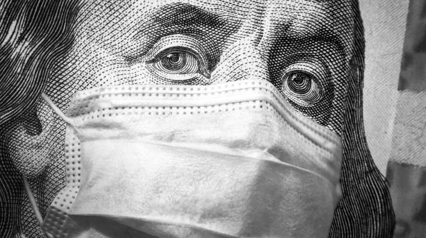 COVID-19 coronavirus, finance and crisis concept, US president Franklin`s eyes and face mask on 100 dollar money bill. Corona virus affects global stock market. stock photo