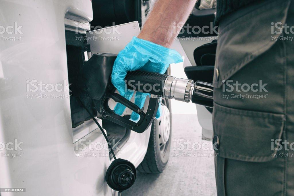 Los precios del gasóleo coronavirus caen al hombre bombeando gasolina en una gasolinera con guante azul médico como COVID-19 difundiendo protección de seguridad para tocar gérmenes - Foto de stock de Agarrar libre de derechos