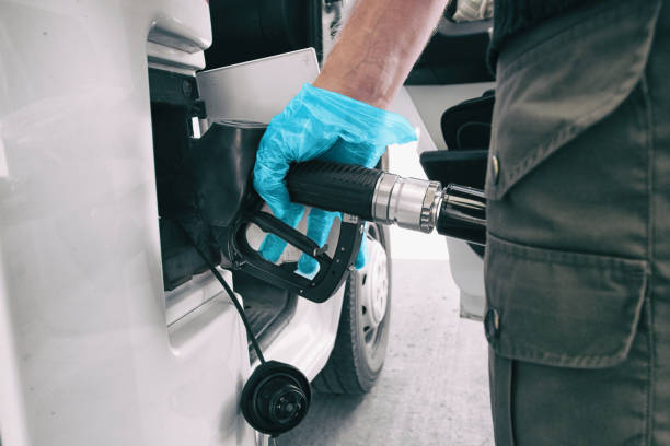 Coronavirus gas oil prices dropping man pumping gasoline at gas station wearing medical blue glove as COVID-19 spreading safety protection for touching germs stock photo
