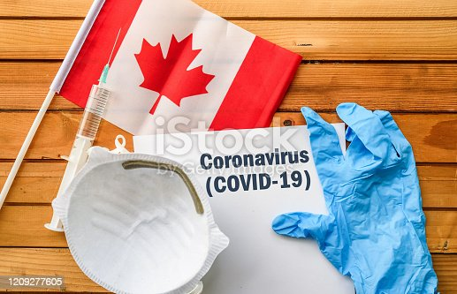 Flag of Canada,, vaccine, face mask for virus, glove and paper sheet with words Coronavirus COVID-19