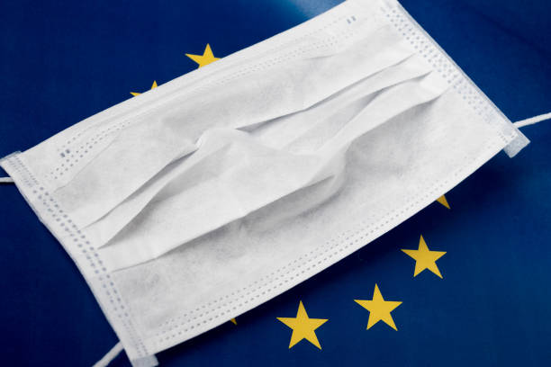 Coronavirus in Europe. Medical antibacterial mask on the background of the flag of the European Union stock photo