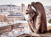COVID-19 coronavirus in France, medical mask on gargoyle of Notre Dame in Paris. Tourist landmarks closed due to corona virus outbreak. Concept of travel, quarantine and COVID coronavirus pandemic.