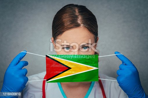 istock Coronavirus in Guyana Female Doctor Portrait hold protect Face surgical medical mask with Guyana National Flag. Illness, Virus Covid-19 in Guyana, concept photo 1219400910