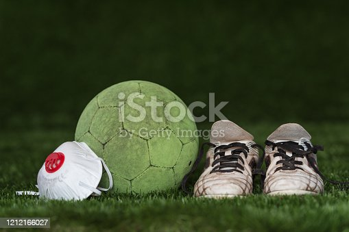 The soccer ball and shoes with face mask as a symbol coronavirus