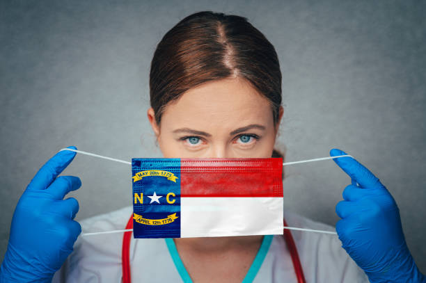 Coronavirus in U.S. State North Carolina, Female Doctor Portrait, protect Face surgical medical mask with North Carolina Flag. Illness, Virus Covid-19 in North Carolina Coronavirus in U.S. State North Carolina, Female Doctor Portrait, protect Face surgical medical mask with North Carolina Flag. Illness, Virus Covid-19 in North Carolina north carolina us state stock pictures, royalty-free photos & images